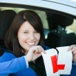 Jolly teen girl sitting in her car tearing a L-sign — Stock Photo #10283780