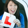 Happy brunette teen girl sitting in her car tearing a L-sign — Stock Photo