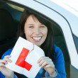 Smiling brunette teen girl sitting in her car tearing a L-sign — Stock Photo