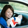 Brunette teen girl sitting in her car tearing a L-sign — Stock Photo