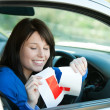 Brunette teen girl sitting in her car tearing a L-sign — Stock Photo #10283813