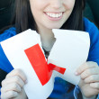 Royalty-Free Stock Photo: Charming teen girl sitting in her car tearing a L-sign