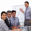 Stock Photo: Cheerful male executive reporting sales figures