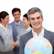 Mature manager holding a terrestrial globe in front of his team — Stock Photo