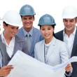 Multi-ethnic architects studying blueprints — Stock Photo