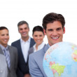 Assertive businessman holding a globe in front of his team — Stock Photo