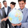 Cheerful businessman holding a globe in front of his team — Lizenzfreies Foto