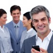 smiling mature manager on phone standig in front of his team — Stock Photo