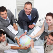 Foto Stock: High angle of smiling business team holding the world