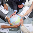 High angle of business team holding a terrestrial globe — Stock Photo