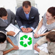 High angle of business team looking at a recycling symbol — Stock Photo