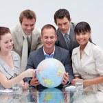 team di business tenendo un globo terrestre. business a livello mondiale — Foto Stock