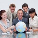 Business team holding a terrestrial globe. International busines — Stock Photo
