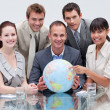 Smiling business team holding a terrestrial globe — Stock Photo #10285349