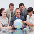 Business team holding terrestrial globe — Photo #10285352