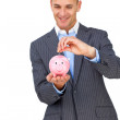 Charismatic businessman saving money in a piggybank — Stock Photo #10285686