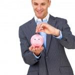 Charismatic businessman saving money in a piggybank — Stock Photo