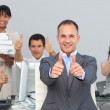 Assertive manager and his team with thumbs up — Stock Photo