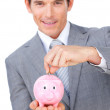Stock Photo: Confident businessman saving money in a piggybank