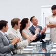 Stock Photo: Business applauding a colleague after giving a presentati