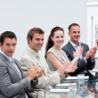 Photo: Business applauding a colleague after reporting to sales