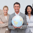 Foto Stock: Business team holding terrestrial globe