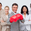 Smiling businessman with boxing gloves leading his team — Stock Photo