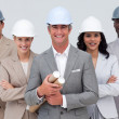 Stock Photo: Architectural team smiling at camerwith hard hats