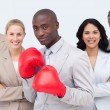 Afro-American businessman with boxing gloves leading his team — Stockfoto