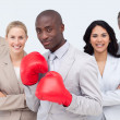 Afro-American businessman with boxing gloves leading his team — Stock Photo