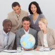 Multi-ethnic business team holding a terrestrial globe — 图库照片
