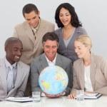 equipo de negocios multiétnica sostiene un globo terrestre — Foto de Stock
