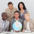 Business team holding a terrestrial globe — Stock Photo