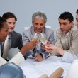 Happy architectutal team celebrating a success with champagne — Stock Photo