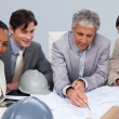 Stock Photo: Architects in a meeting studying plans