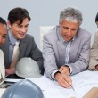 Architects in meeting studying plans — Stock Photo #10286541