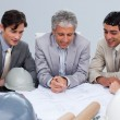 Engineers in a meeting studying plans — Stock Photo