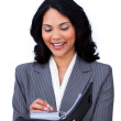 Ethnic businesswoman making notes on her agenda — Stockfoto