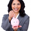 Cheerful businesswoman saving money in a piggybank — Stock fotografie