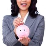 Positive businesswoman saving money in a piggybank — Stock Photo #10286652