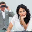 Brunette businesswoman annoyed by a man looking through binocula — Stock Photo