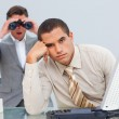 Handsome businessman getting bored and his manager looking throu — Stock Photo