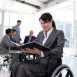 Stock Photo: Businesswoman in a wheelchair reading a report