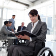 Businesswomin wheelchair reading report — Stock Photo #10287448