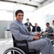 Young businessman in a wheelchair at a meeting — Stock Photo