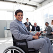 Young businessman in a wheelchair at a meeting - Stock Photo
