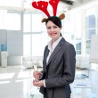 Smiling businesswoman with a novelty Christmas hat drinking Cham — Stock Photo