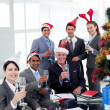Business with novelty Christmas hat toasting at a party - Stock Photo