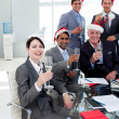 Manager and his team with novelty Christmas hat toasting at a pa - Stock Photo