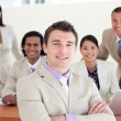 Confident manager with folded arms in front of his team — Stock Photo #10288205